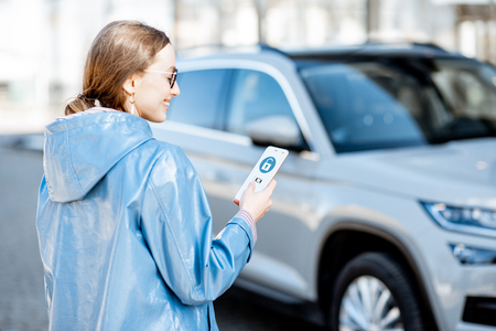 Woman unlocking car using mobile application on a smart phone. Concept of a remote control and car protection through the internet