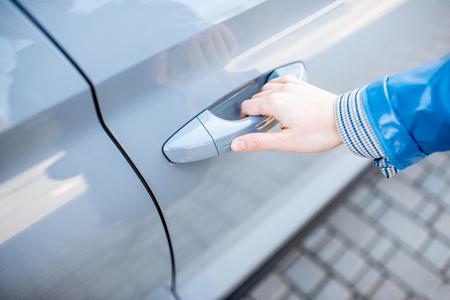 Frau zieht Türgriff des modernen Autos, Nahaufnahme. Konzept des schlüssellosen Zugangs zum Auto