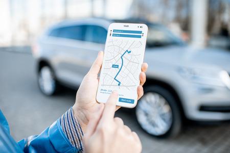 Kobieta korzystająca ze smartfona z aplikacją nawigacyjną, zbliżenie z nowoczesnym samochodem w tle
