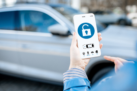 Unlocking car using mobile application on a smart phone. Concept of remote control and car protection through the internet Banco de Imagens