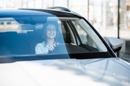 Young and happy woman driving a luxury car in the city, front view through the windshield Stockfoto