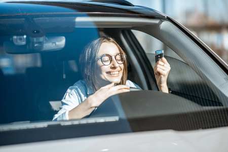 Portrait of a young woman with excited emotions holding keys in the new car