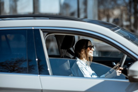 Young and happy woman driving luxury car in the city, side view through the door window Stock Photo
