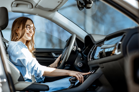 Young woman controlling air conditioner, touching the dashboard of the modern car in the city