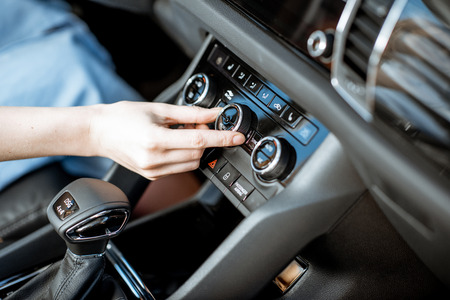 Mujer girando la rueda del aire acondicionado en el coche, vista cercana Foto de archivo