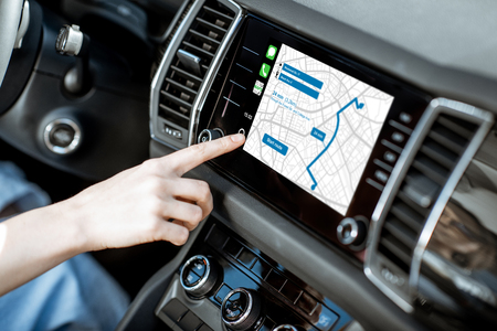 Touching a monitor with navigation map of the modern car, close-up view Фото со стока
