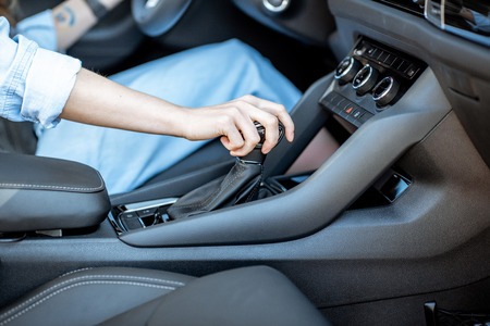 Woman switching gear, holding handle of the automatic gearbox of the modern car, close-up view