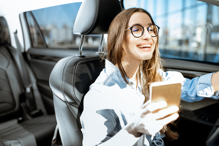 Young and cheerful woman using smart phone while driving a modern car in the city Imagens