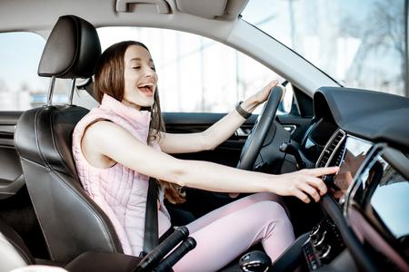 Junge und fröhliche Frau in rosa Sportkleidung, die Musik hört, während sie ein Luxusauto in der Stadt fährt