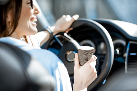 Cheerful woman holding steering wheel and coffe cup while driving a car, close-up view