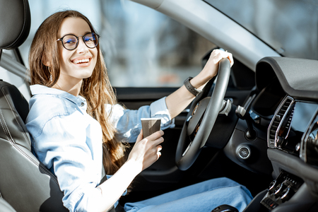 Portrait of a young and cheerful woman with coffee cup driving luxury car in the city