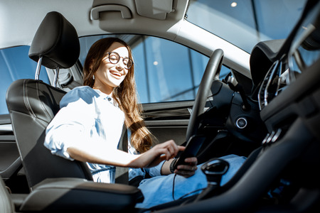 Young and cheerful woman using smart phone while sitting in the modern car in the city Imagens