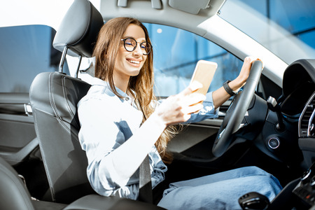 Young and cheerful woman using smart phone while driving a modern car in the city Banque d'images