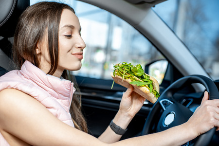 Young and cheerful woman in sportswear eating healthy sandwich with salad while driving car in the city 版權商用圖片