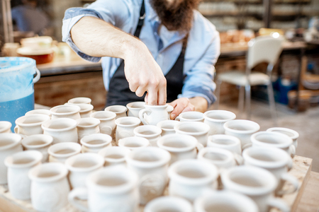 Man taking clay jugs for painting at the pottery shop, close-up view Stock fotó - 120220545