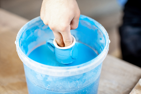 Painting clay jugs, diving into the bucket with blue paint, close-up view