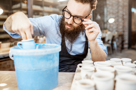 Handsome bearded worker painting clay jugs, diving products into the bucket with blue paint at the pottery shop Foto de archivo
