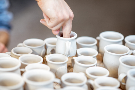 Man taking clay jugs for painting at the pottery shop, close-up view Reklamní fotografie
