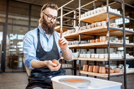 Gut aussehender Mann in Schürze, der Ton vorbereitet, während er Krüge auf der Töpferscheibe bei der Herstellung herstellt