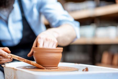 Homme faisant une cruche en argile formant une forme à la main sur le tour de potier à l'intérieur, vue rapprochée Banque d'images