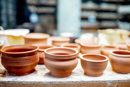 Close-up of clay pitchers before baking on the shelves at the pottery