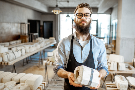 Portrait of a handsome worker standing with gypsum form at the pottery manufacturing Stock Photo