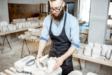 Handsome worker in apron getting clay products from the gypsum forms at the pottery manufacturing Reklamní fotografie