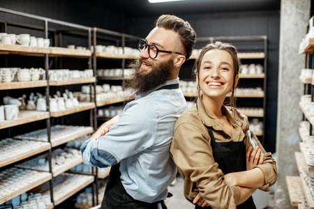 Portrait of young man and woman as a workers or business owners in the pottery shop