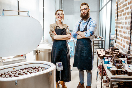 Portrait of a man and woman as a workers or business owners standing at the pottery manufacturing
