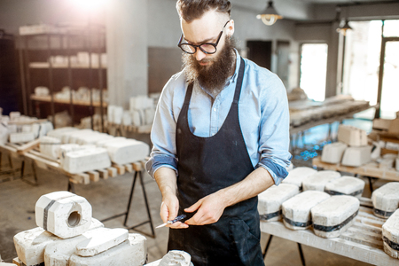 Handsome worker in apron getting clay products from the gypsum forms at the pottery manufacturing Stock Photo