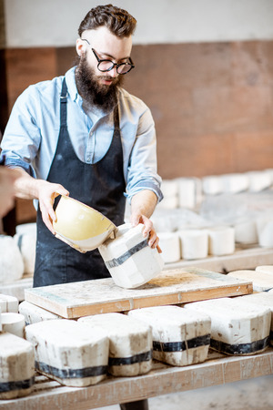 Handsome worker pouring special liquid into the gypsum form at the pottery manufacturing Stock Photo