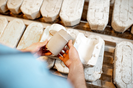 Male worker getting clay products from the gypsum forms at the pottery manufacturing, close-up view