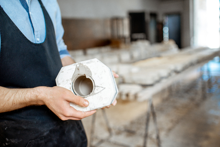 Man holding gypsum form at the pottery manufacturing, close-up view Stock Photo
