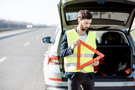 Man in road vest holding emergency triangle sign near the broken car on the roadside