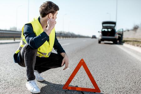 Homme avec des émotions de désespoir assis près du panneau d'urgence au bord de la route avec une voiture cassée en arrière-plan
