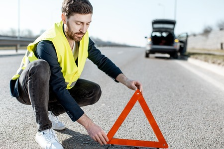 Man in road vest putting emergency triangle sign on the highway with broken car on the background