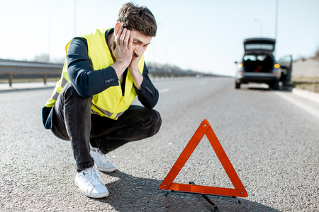 Man with despair emotions sitting near the emergency sign on the roadside with broken car on the background