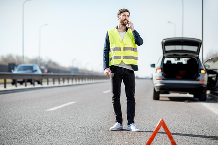 Mann in Weste, der die Pannenhilfe anruft, die in der Nähe des kaputten Autos auf der Autobahn steht Standard-Bild