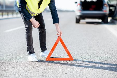 道路ベストの男は、背景に壊れた車で高速道路に緊急三角形の看板を置く、クローズアップビュー