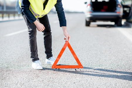 Hombre en chaleco de carretera poniendo señal triangular de emergencia en la carretera con coche roto en el fondo, vista de primer plano