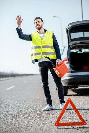 Man stopping car standing with refuel canister on the roadside having no gasoline in his tank