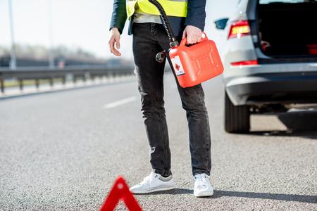 Hombre con recipiente de repostaje en el borde de la carretera con su coche en el fondo, vista cercana sin rostro Foto de archivo
