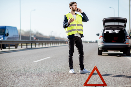 Man in vest calling road assistance standing near the broken car on the highway