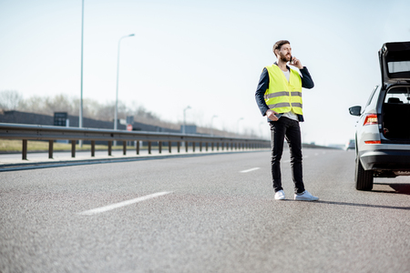 Man in vest calling road assistance standing near the broken car on the highway, wide view with copy space Archivio Fotografico