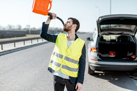 Lustiges Porträt eines Mannes, der aus der Tankdose trinkt, in der Nähe des kaputten Autos am Straßenrand Standard-Bild