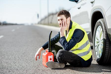 Man met wanhoopsemoties zittend met tankbus bij zijn auto langs de weg Stockfoto