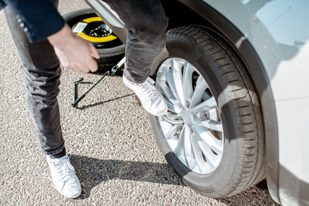 Man unscrewing the broken wheel on the roadside, close-up view