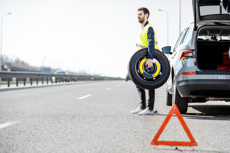 Man changing wheel standing with spare wheel near the broken car on the roadside