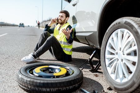 Man calling the road assistance sitting near the car with broken wheel on the roadside
