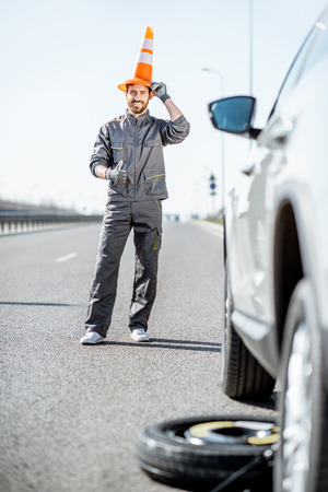 Funny portrait of a road assistance worker with emergency cone near the car on the highway